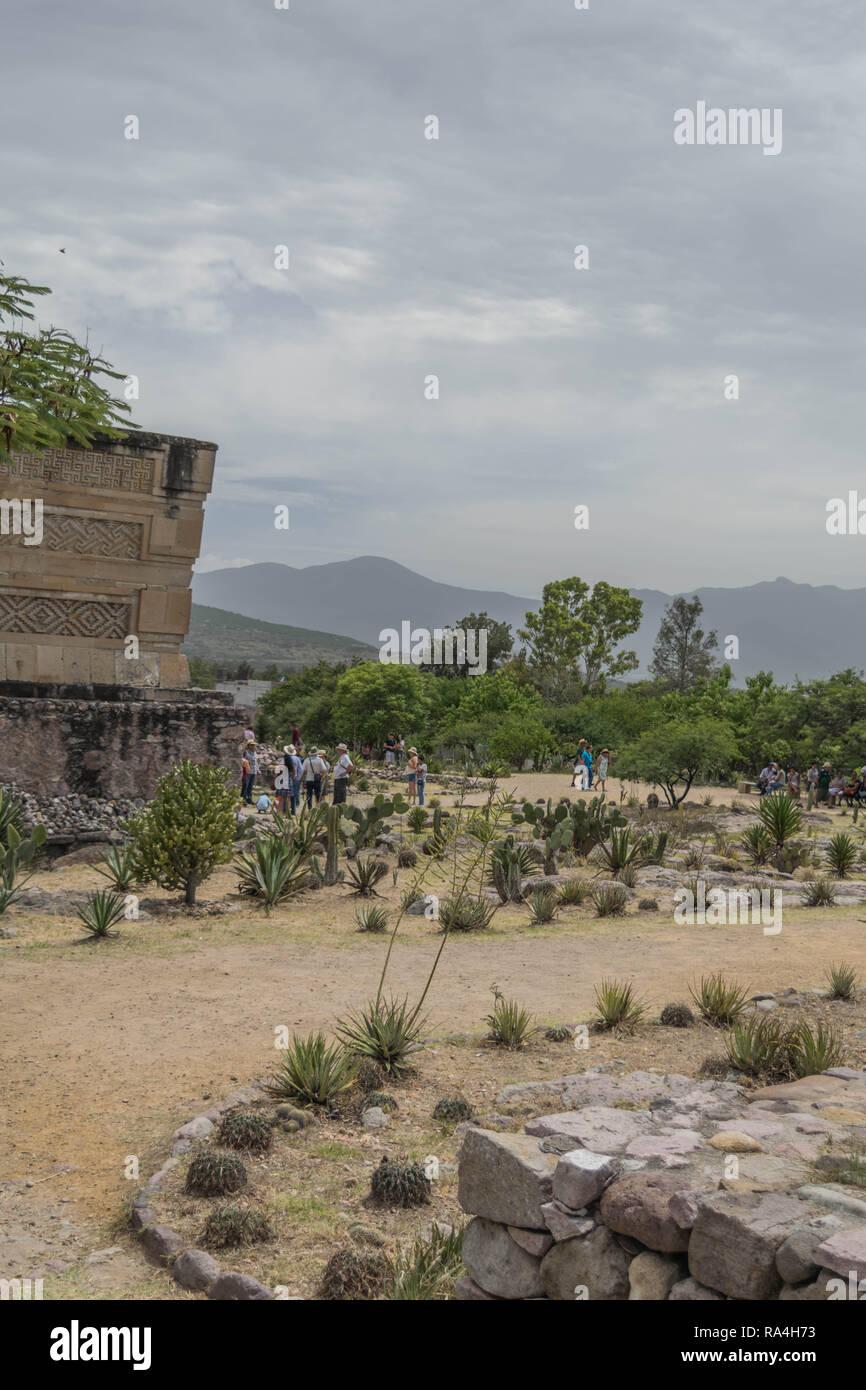 Ruines Zapotèques antiques à Mitla, avec un sentier sinueux, les touristes et les montagnes en arrière-plan, à Oaxaca, Mexique Photo Stock