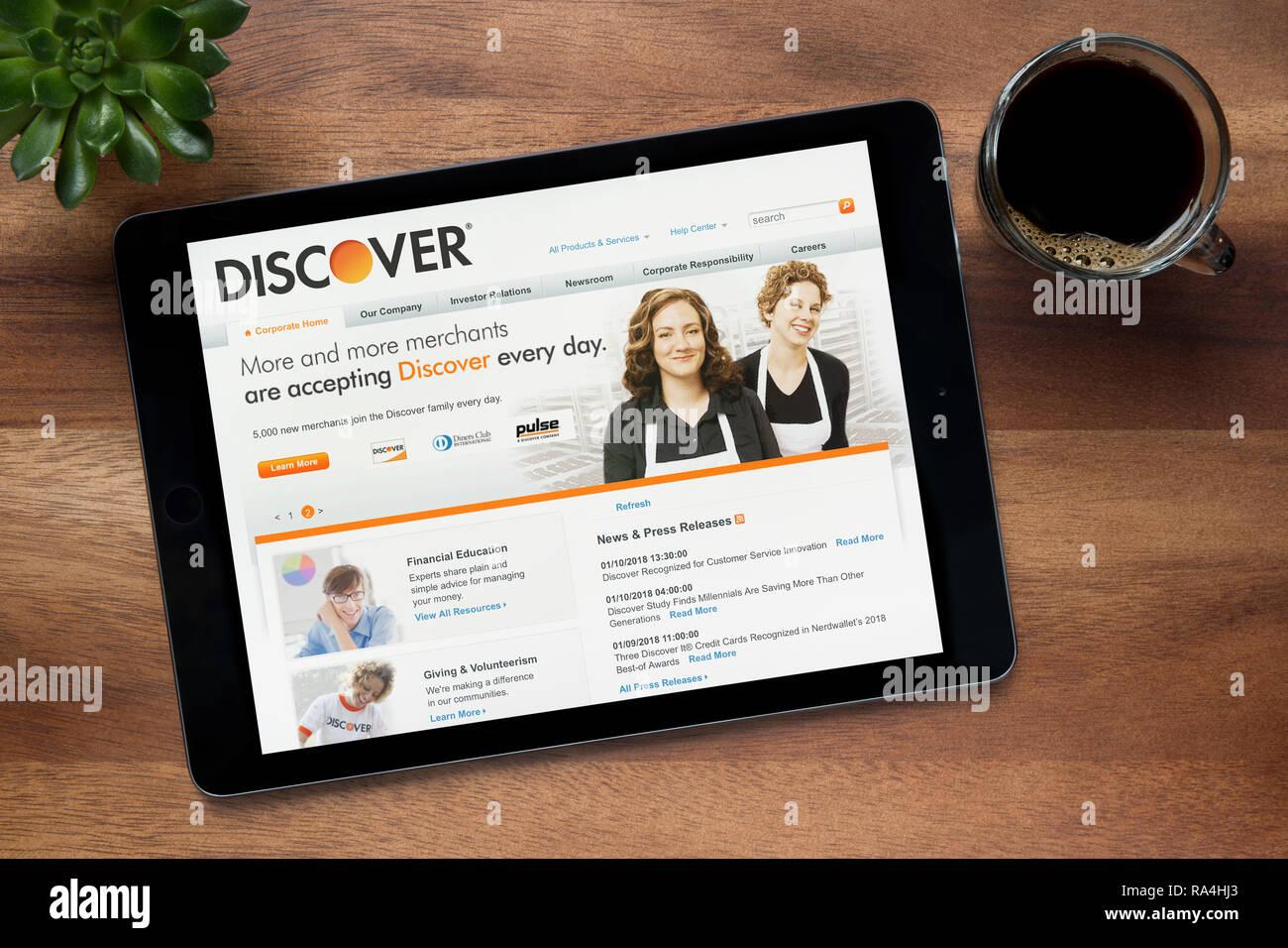 Le site internet de Discover.com est vu sur un iPad tablet, sur une table en bois avec une machine à expresso et d'une plante (usage éditorial uniquement). Photo Stock