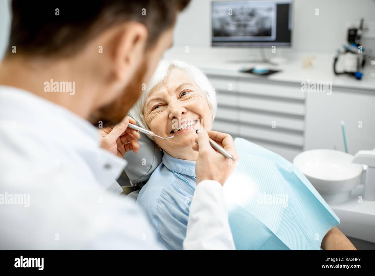 Femme âgée lors de l'examen médical auprès d'un dentiste dans le cabinet dentaire Banque D'Images