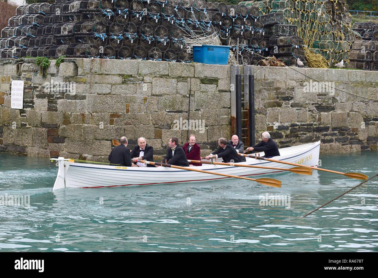 Newquay, Cornwall, UK. 21 avril, 2018. Les principaux membres de Newquay Rowing Club de porter des smokings sur leur rapport annuel Port d'Run'. Une bouteille de porto est ramé à travers la baie de Newquay à île de Porth par ces rameurs dans un pilote traditionnel cornouaillais Gig. Une fois qu'ils la bouteille est consommée par les rameurs qui puis revenir au port de Newquay. Gordon 1928/Alamy Live News. Photo Stock