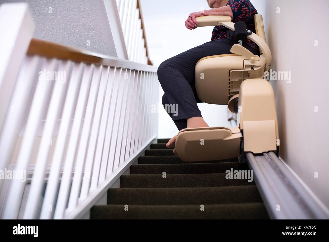 Détail de Senior Woman Sitting on monte-escalier à la maison pour aider à la mobilité Photo Stock