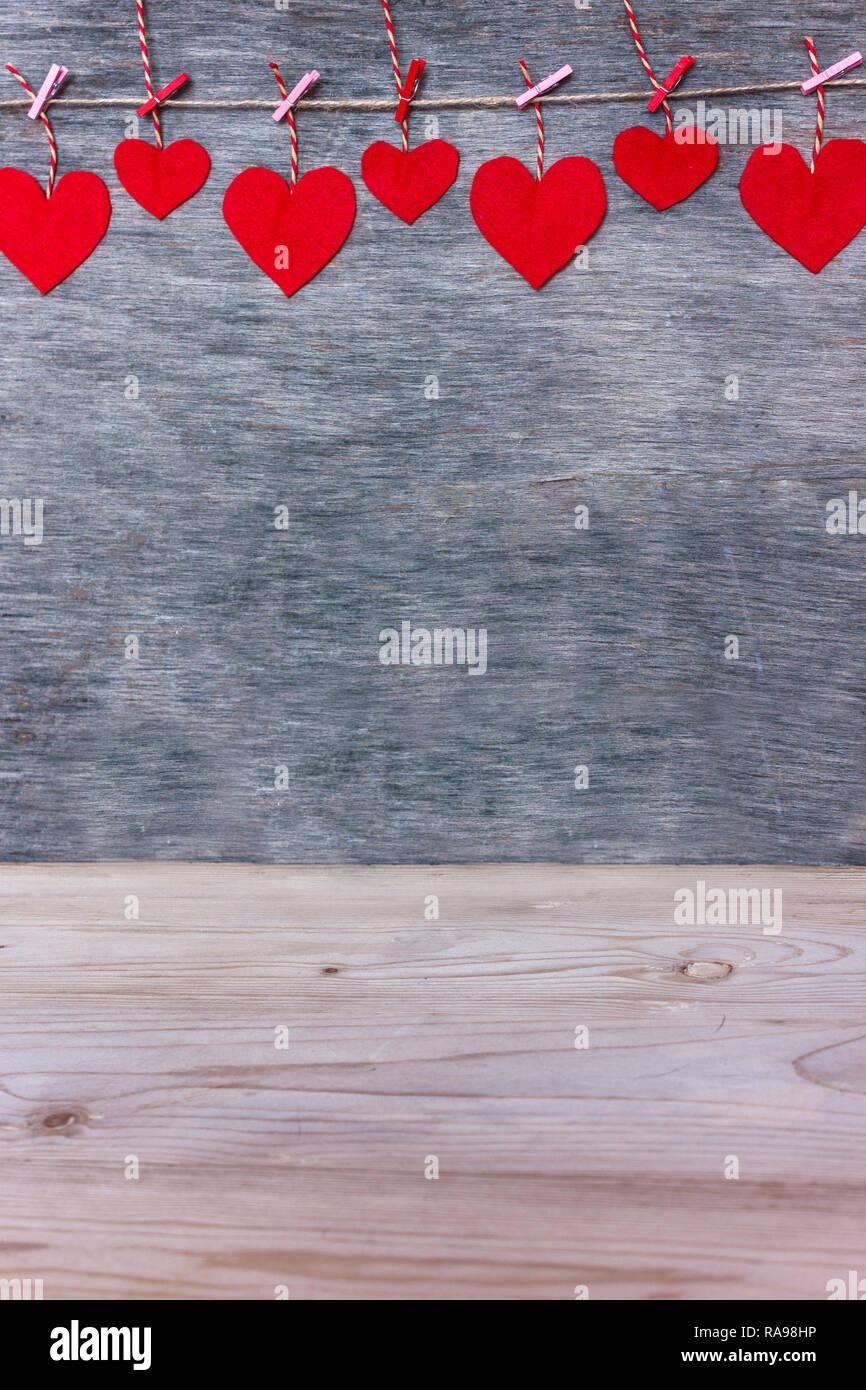 Amour Saint Valentin coeurs rouge sur cordon rose naturel et les axes de pendaison sur fond texture rustique, copy space Photo Stock