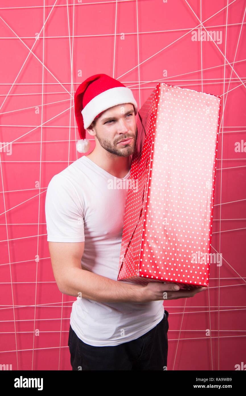 Prêt à déballer votre cadeau. Vacances de Noël la célébration. L'homme non rasé beau santa hat attente boîte-cadeau. Concept de cadeau de Noël. Santa apporter en cadeau pour vous. L'homme beau père noël faire grande boîte. Photo Stock