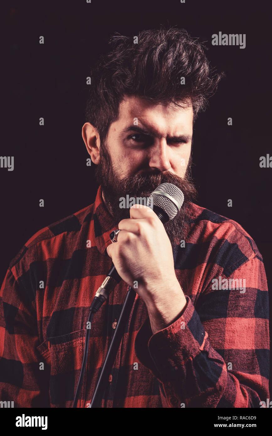 Musicien, chanteur chantant en music hall, club. Musicien avec barbe et moustache éclairé par des projecteurs. Concept du chanteur. Homme avec tendue face strict est titulaire d'un micro, chantant la chanson, fond noir. Photo Stock