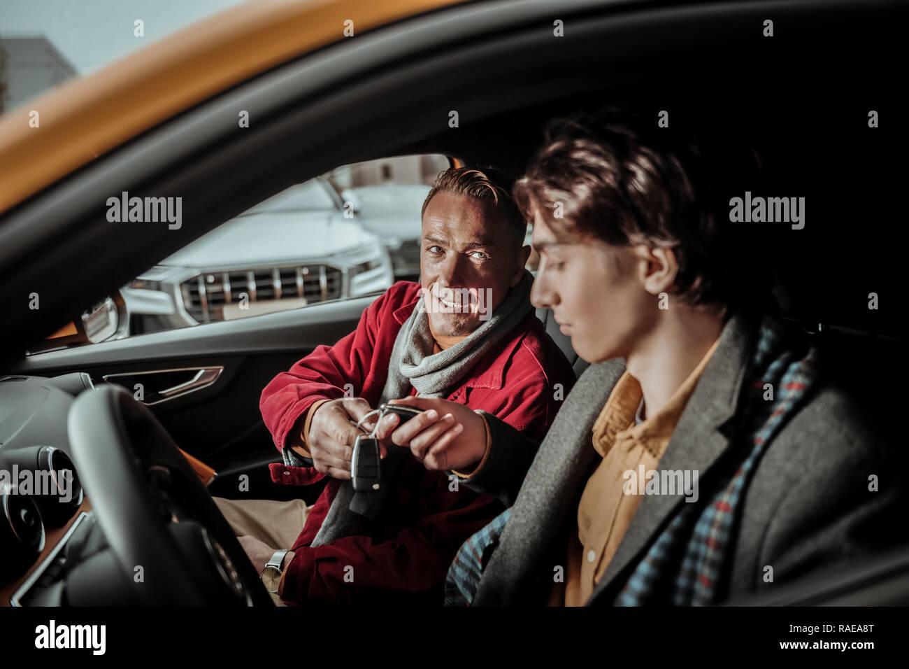 Sentiment généreux père heureux de présenter des clés de voiture à son fils Photo Stock