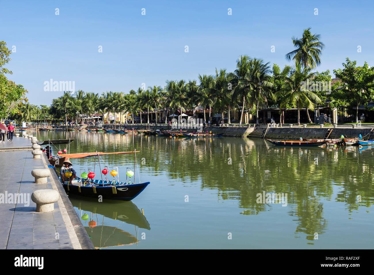 Les petits bateaux traditionnels sur la rivière Thu Bon et bordée de palmiers dans le vieux quartier de la ville historique. Hoi An, Quang Nam, Vietnam, Asie Photo Stock