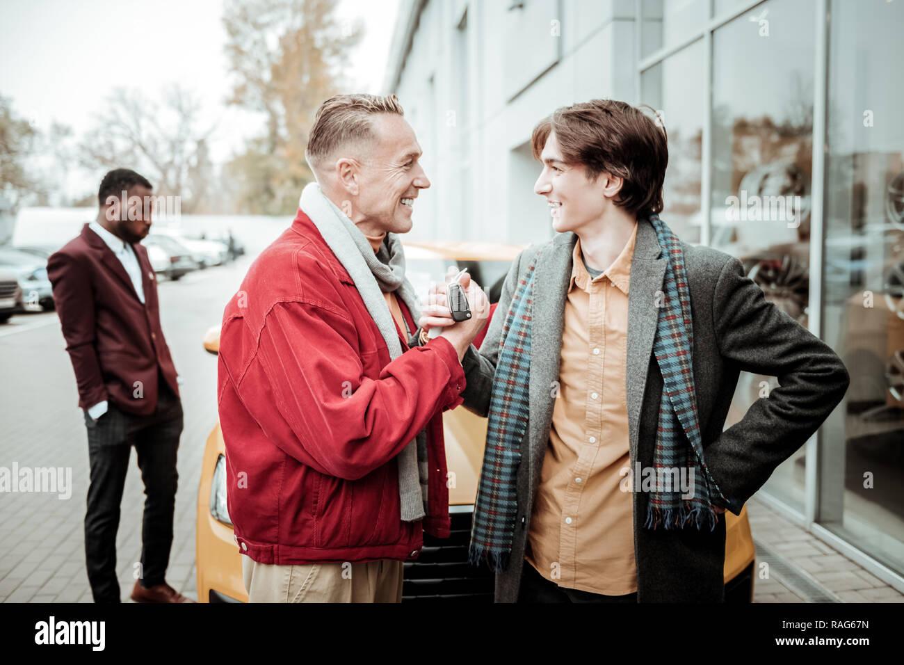 Généreux père aimant présentant son jeune fils les clés de voiture Photo Stock