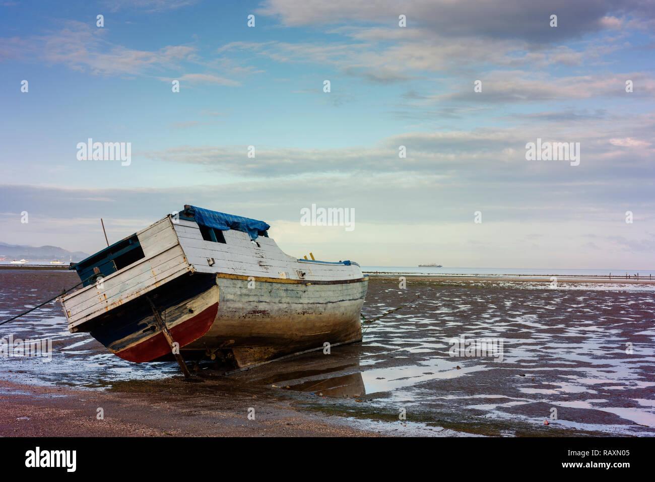 Un bateau traditionnel se trouve sur le sable à marée basse à Dili. Banque D'Images