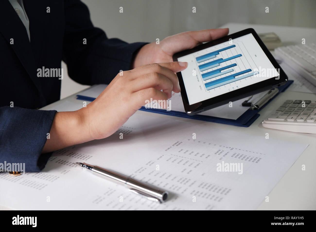 Les femmes travaillant dans le bureau. L'analyse financière avec les graphiques de pad pour l'entreprise, comptabilité, assurances et finances concept Banque D'Images
