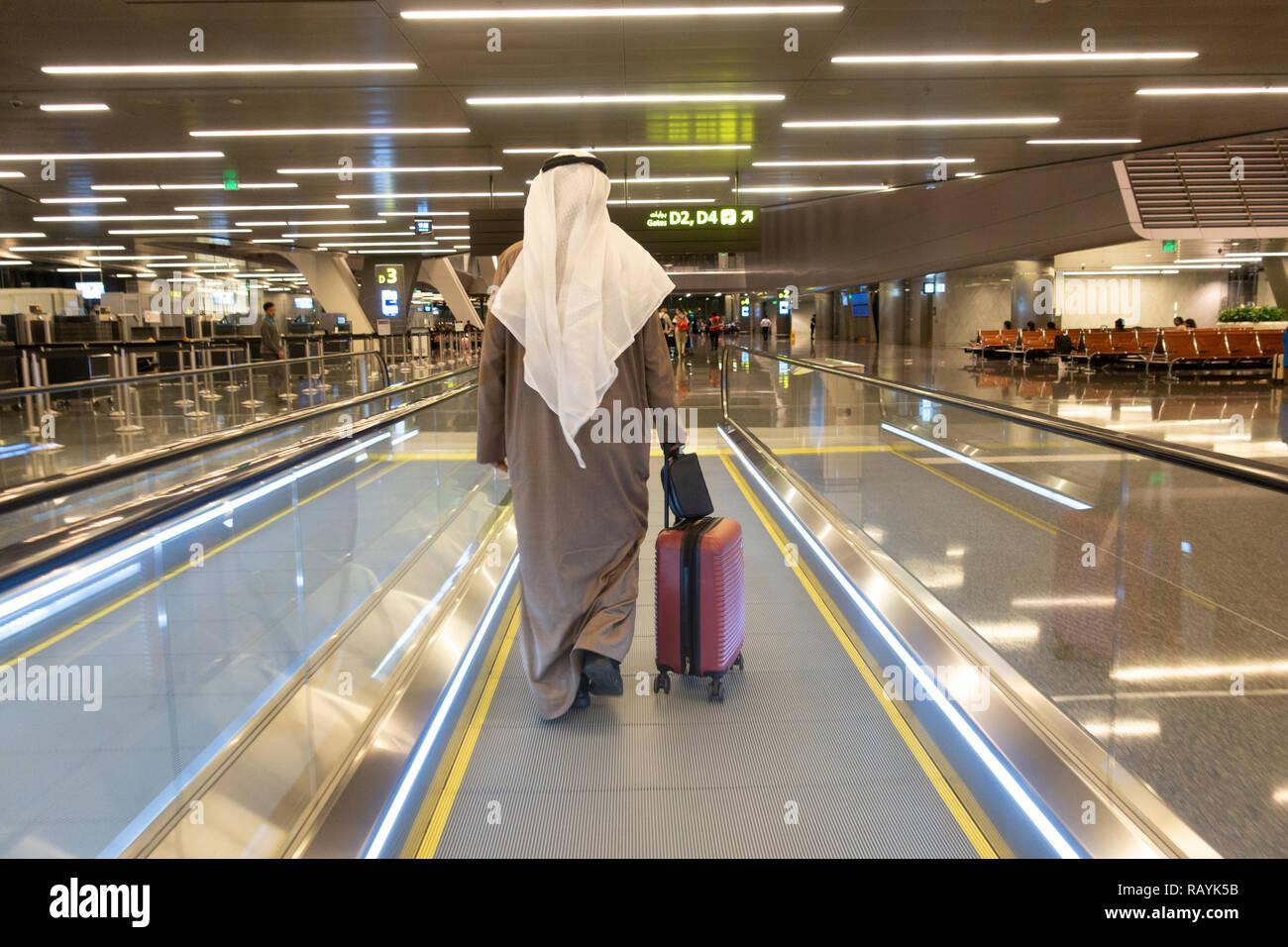 Passagers arabes sur tapis roulant au terminal de l'Aéroport International Hamad moderne à Doha, Qatar Banque D'Images