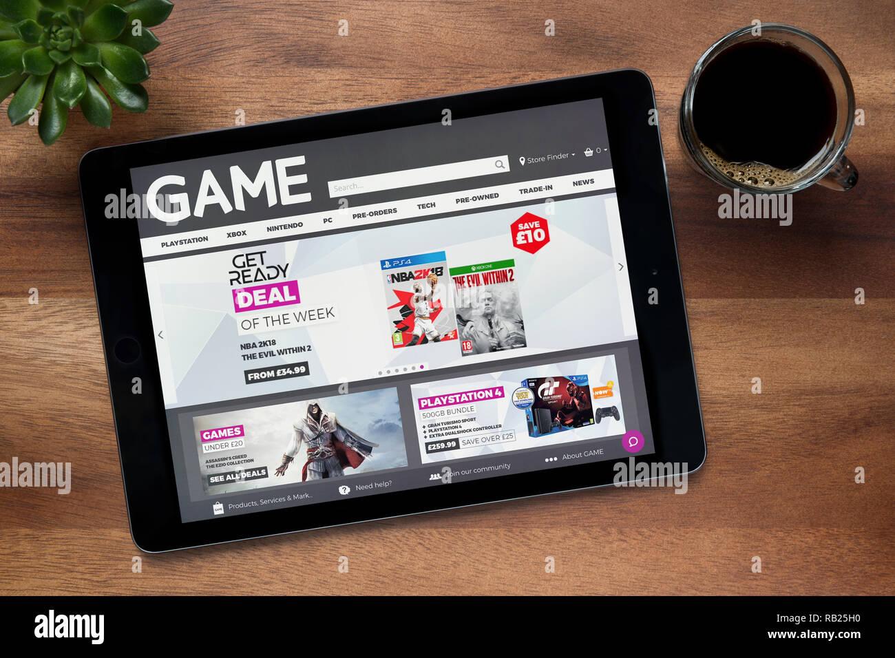 Le site internet de jeu détaillant est vu sur une tablette iPad, sur une table en bois avec une machine à expresso et d'une plante (usage éditorial uniquement). Photo Stock