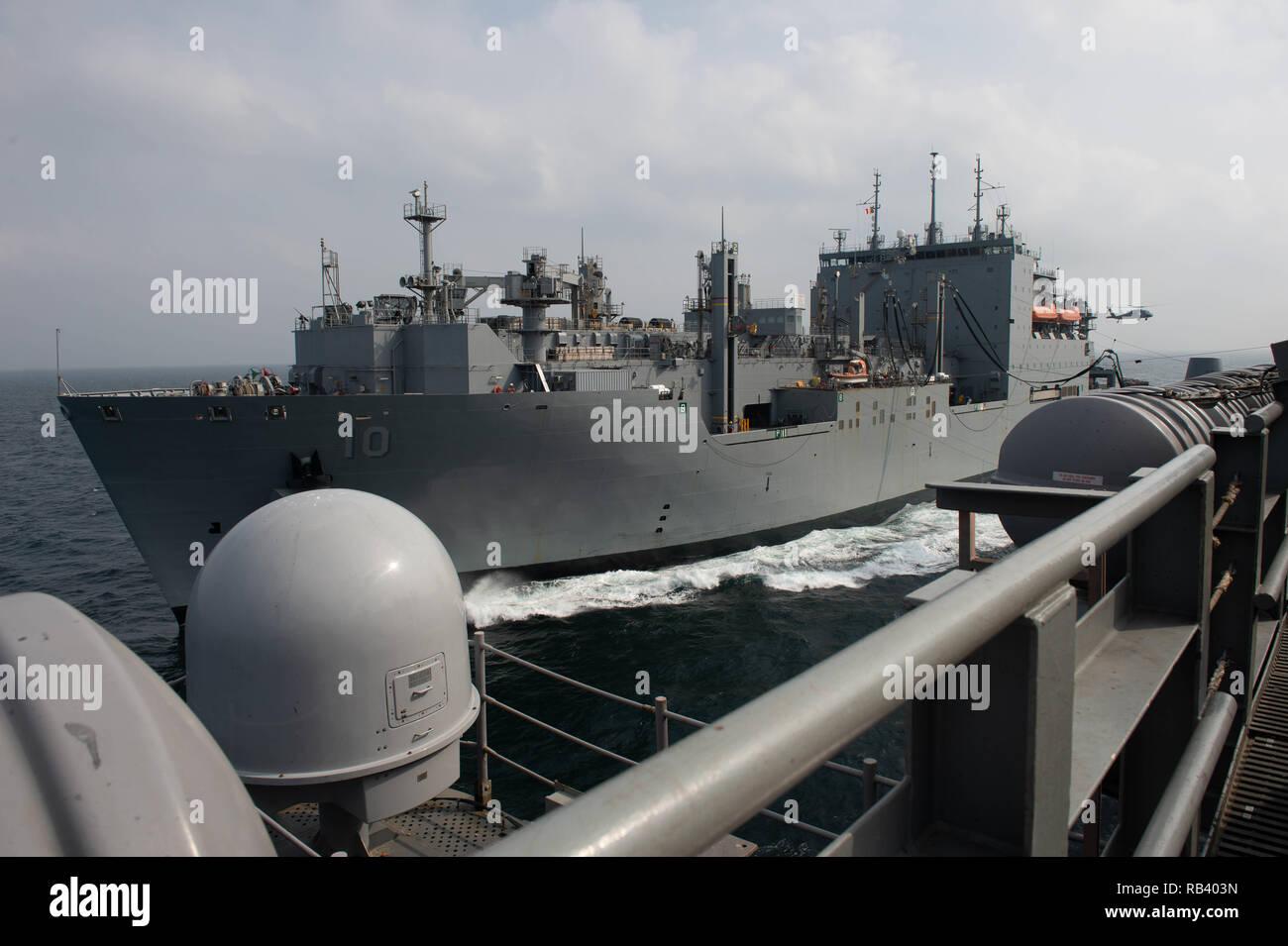 Les cargaisons sèches et de munitions ship USNS Charles Drew (T-AKE 10) voiles aux côtés du porte-avions USS JOHN C. STENNIS (CVN 74) au cours d'un ravitaillement en mer dans le Golfe Arabe, le 4 janvier 2019. Le John C. Stennis dans le groupe est déployé pour la 5e flotte américaine zone d'opérations à l'appui des opérations navales pour assurer la stabilité et la sécurité maritime dans la région Centrale, reliant la Méditerranée et le Pacifique à travers l'ouest de l'Océan indien et trois points d'étranglement stratégiques. (US Navy photo de Mass Communication Specialist Seaman Apprentice Jordanie Ripley) Photo Stock