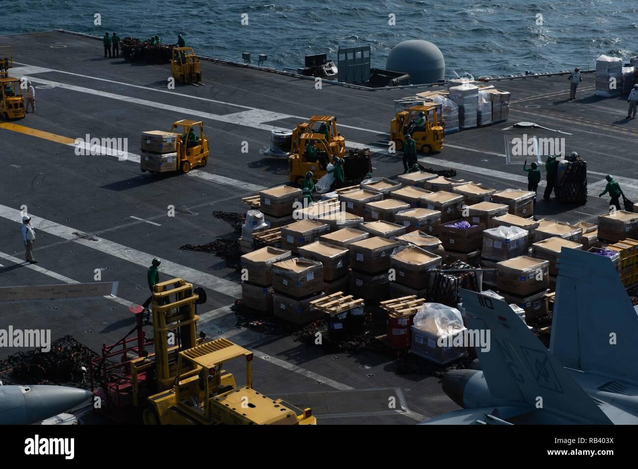 Les marins américains organiser au cours d'un cargo de ravitaillement vertical sur le pont du porte-avions USS JOHN C. STENNIS (CVN 74) dans la région du Golfe, le 4 janvier 2019. Le John C. Stennis dans le groupe est déployé pour la 5e flotte américaine zone d'opérations à l'appui des opérations navales pour assurer la stabilité et la sécurité maritime dans la région Centrale, reliant la Méditerranée et le Pacifique à travers l'ouest de l'Océan indien et trois points d'étranglement stratégiques. (US Navy photo de Mass Communication Specialist Seaman Apprentice Jordanie Ripley) Photo Stock