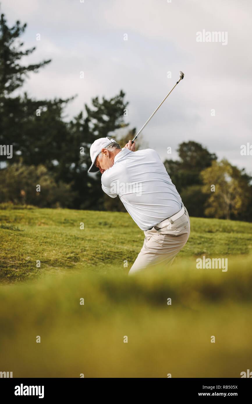 Golfeur aîné professionnel jouer au golf sur le parcours. L'homme de frapper la balle d'un bunker de sable. Banque D'Images