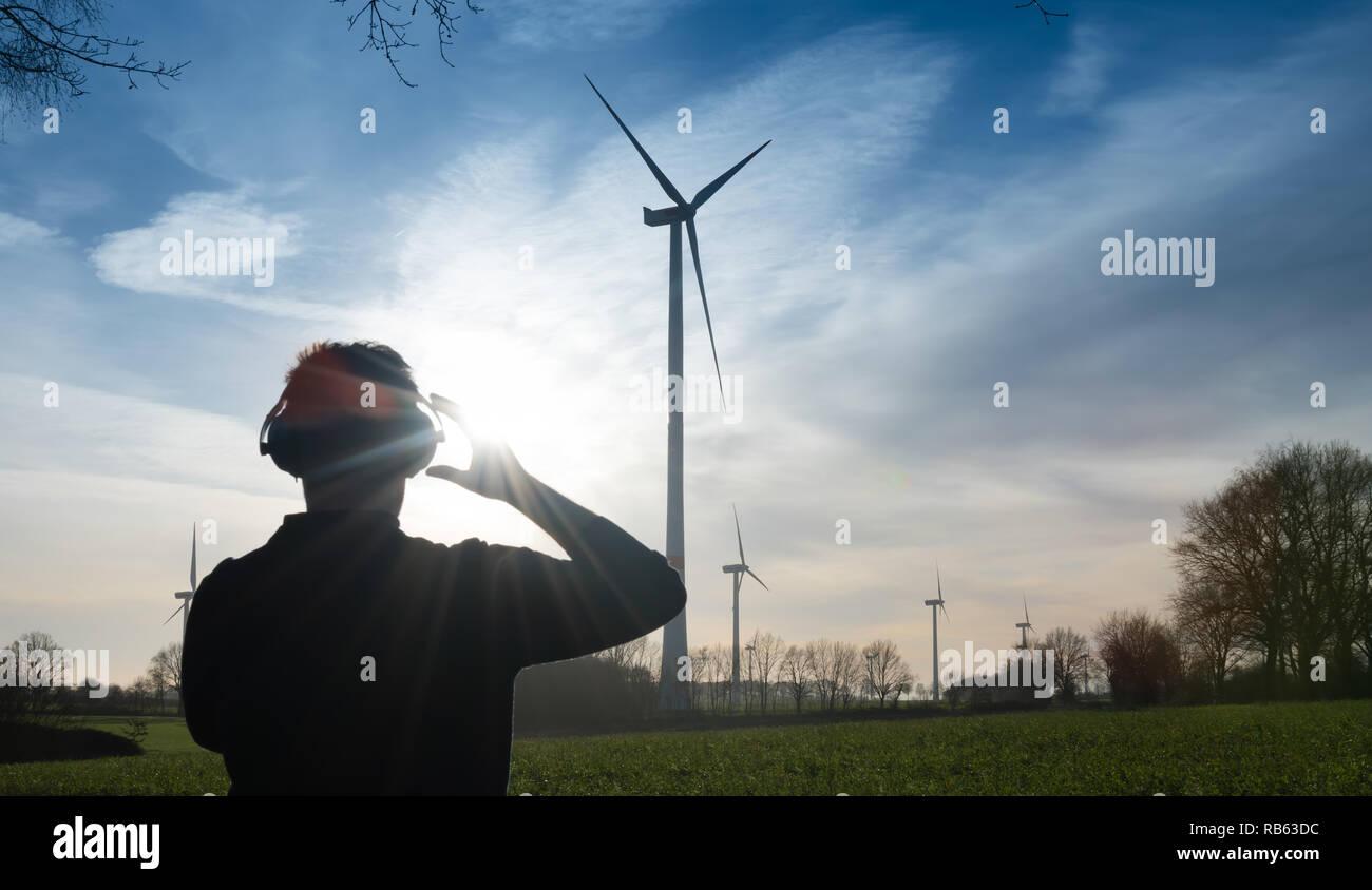 L'homme en face d'une ferme éolienne utilise protecteur de bruit pour réduire le bruit de l'éolienne Photo Stock