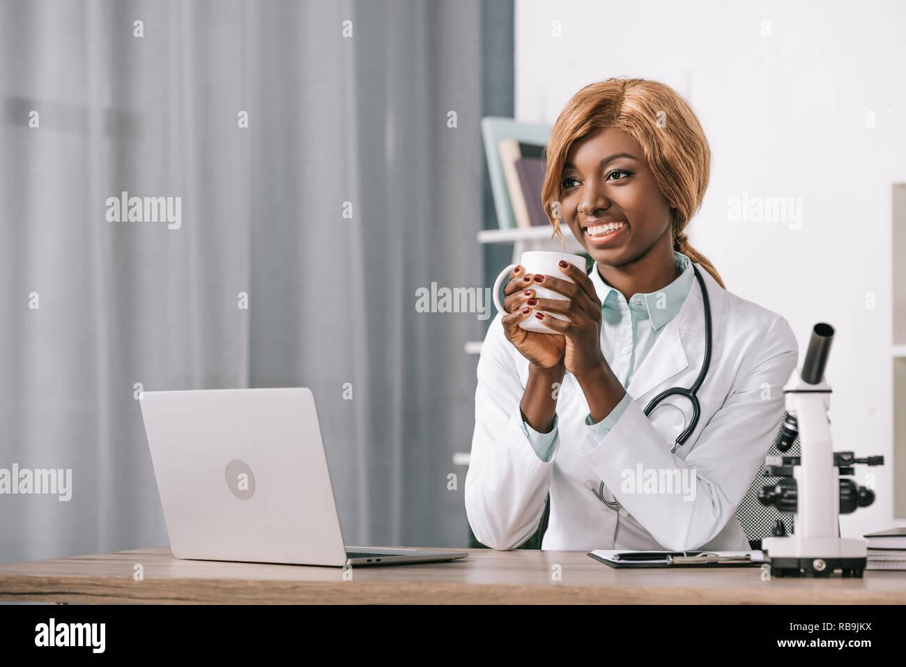 Belle african american scientist holding cup avec boisson Banque D'Images
