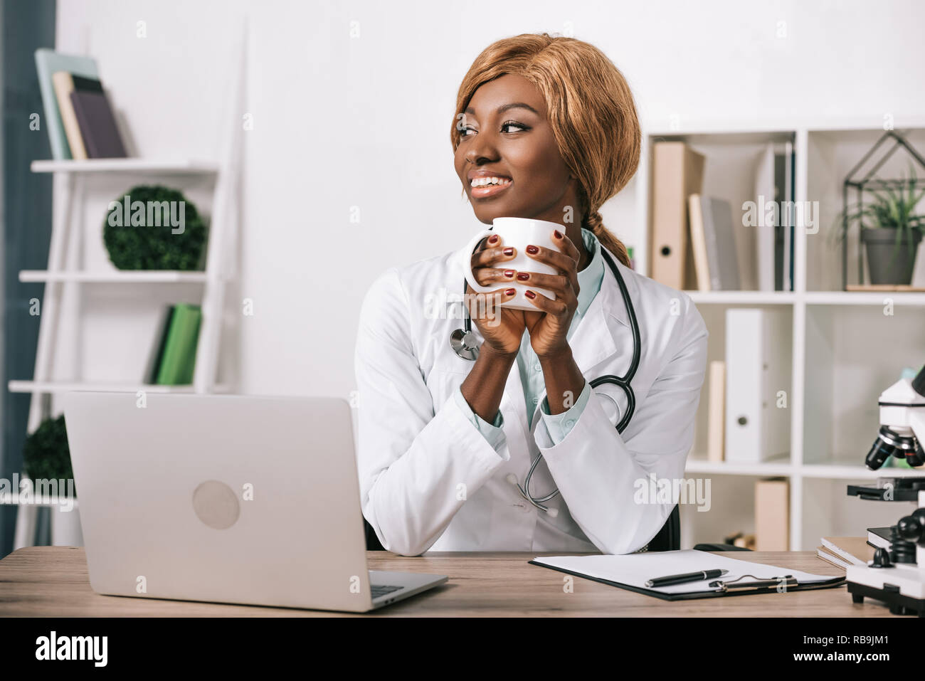 African American female scientist holding cup Banque D'Images