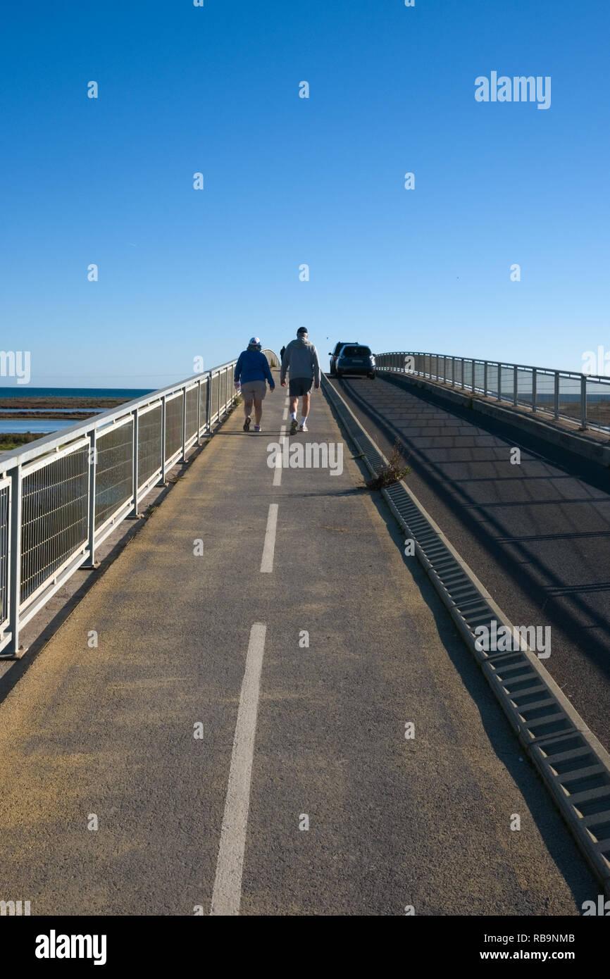 Deux vieilles gens habillés pour la marche, marche sur un pont sur le Canal du Midi en France sur une journée ensoleillée d'automne Photo Stock