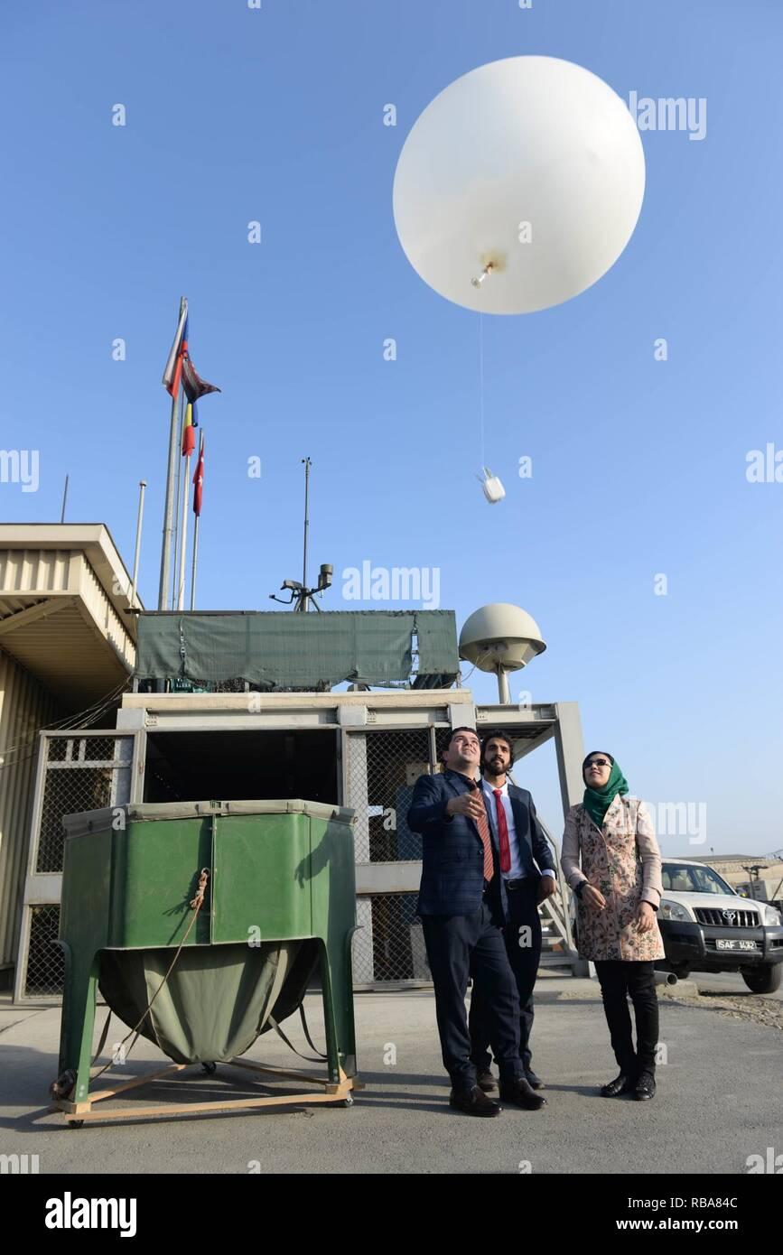 Trois météorologues afghans relâcher un ballon météo à l'Aéroport International d'Hamid Karzaï au cours d'une cérémonie qui marque leur intégration à l'office de météorologie de l'OTAN, à Kaboul, Afghanistan, 1 janvier, 2017. Au total, 10 météorologues Afghans vont rejoindre le bureau afin de renforcer les capacités d'un de l'aéroport par des fonctions essentielles pour les opérations. (L'OTAN Banque D'Images