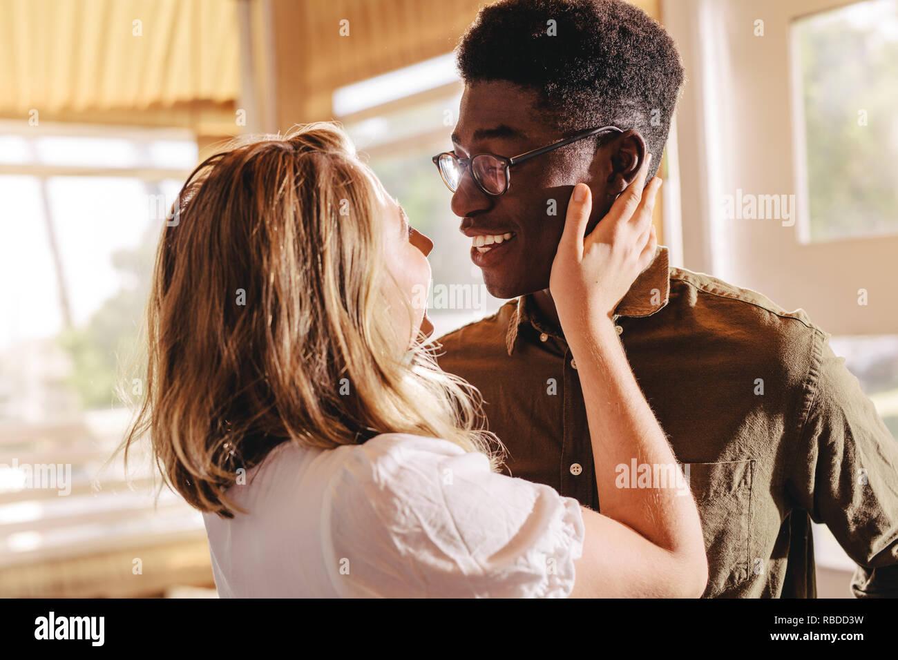Beau couple interracial à uns les autres avec amour tout en se tenant à l'intérieur. L'homme et de la femme romantique enlacés. Banque D'Images