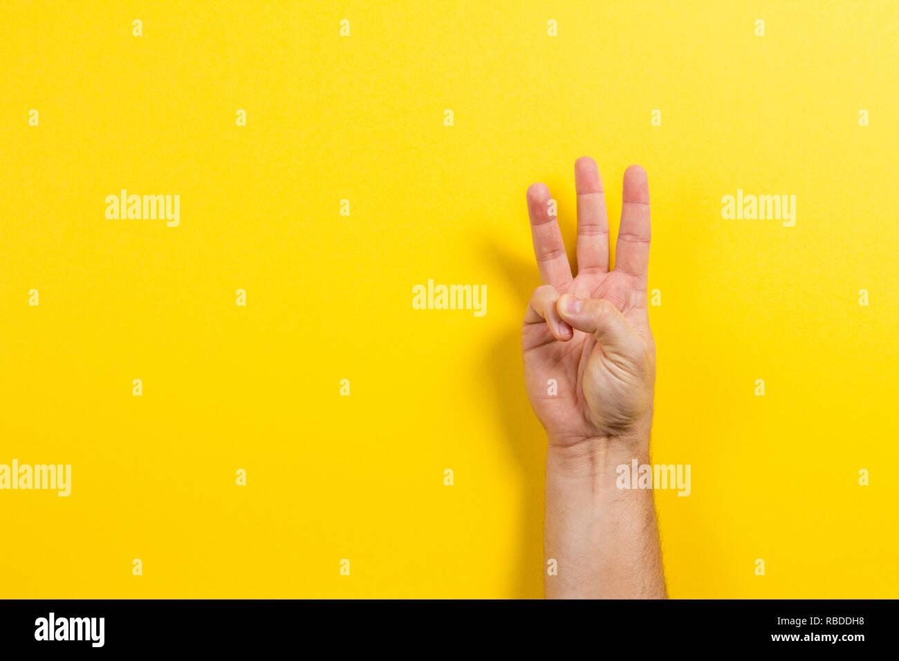 Man main montrant trois doigts sur fond jaune. Symbole numéro deux Photo Stock