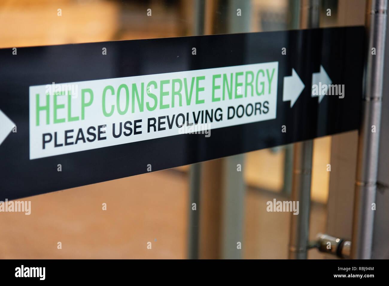 Un panneau dans un immeuble Toronto disant aider économiser de l'énergie - Veuillez utiliser des portes tournantes Photo Stock