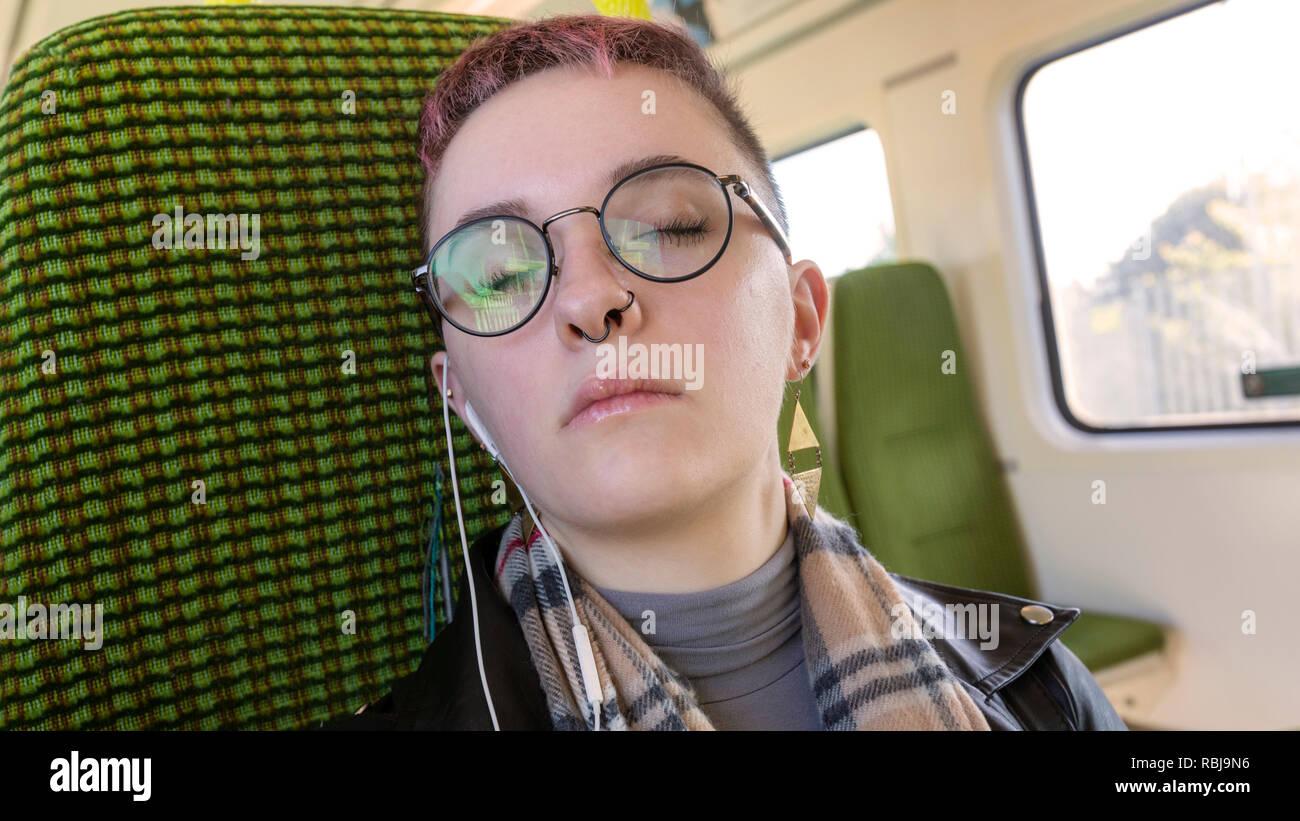 Jeune femme se reposer ses yeux et équitation sur la DART, le transport public, à Dublin, Irlande. Photo Stock