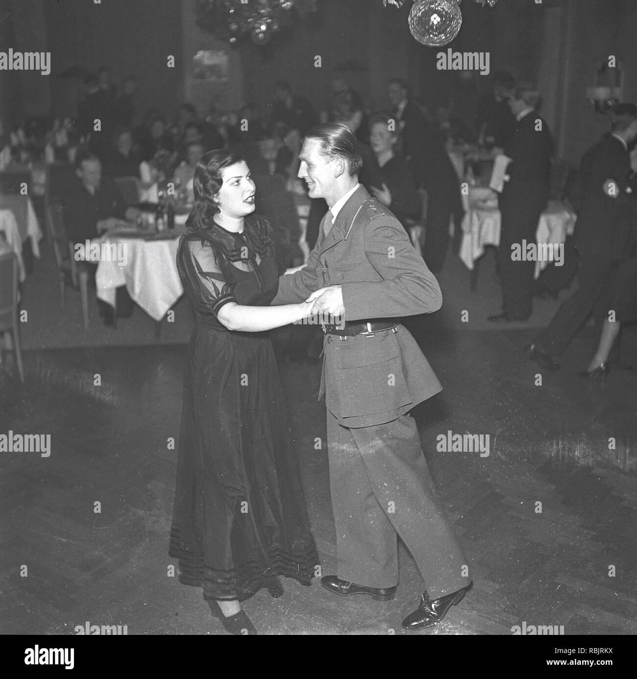 La danse dans les années 40. Un couple est la danse et se tenant à proximité, déménagement à la musique à un événement de danse. La photo a été utilisée dans un article de l'époque pour illustrer le thème de femmes espions durant la seconde guerre mondiale. Apparemment innocente d'une jeune femme séduisante et romances un soldat et obtient les informations à transmettre. Kristoffersson Photo Ref 225-32. Suède 1941 Photo Stock