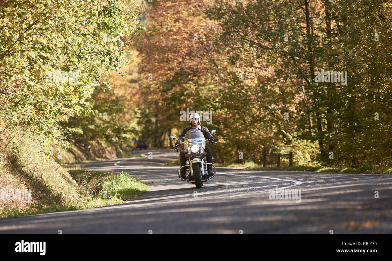 b83b1796c2b910 Casque de motocycliste barbu, lunettes et vêtements de cuir noir moto  équitation le long de