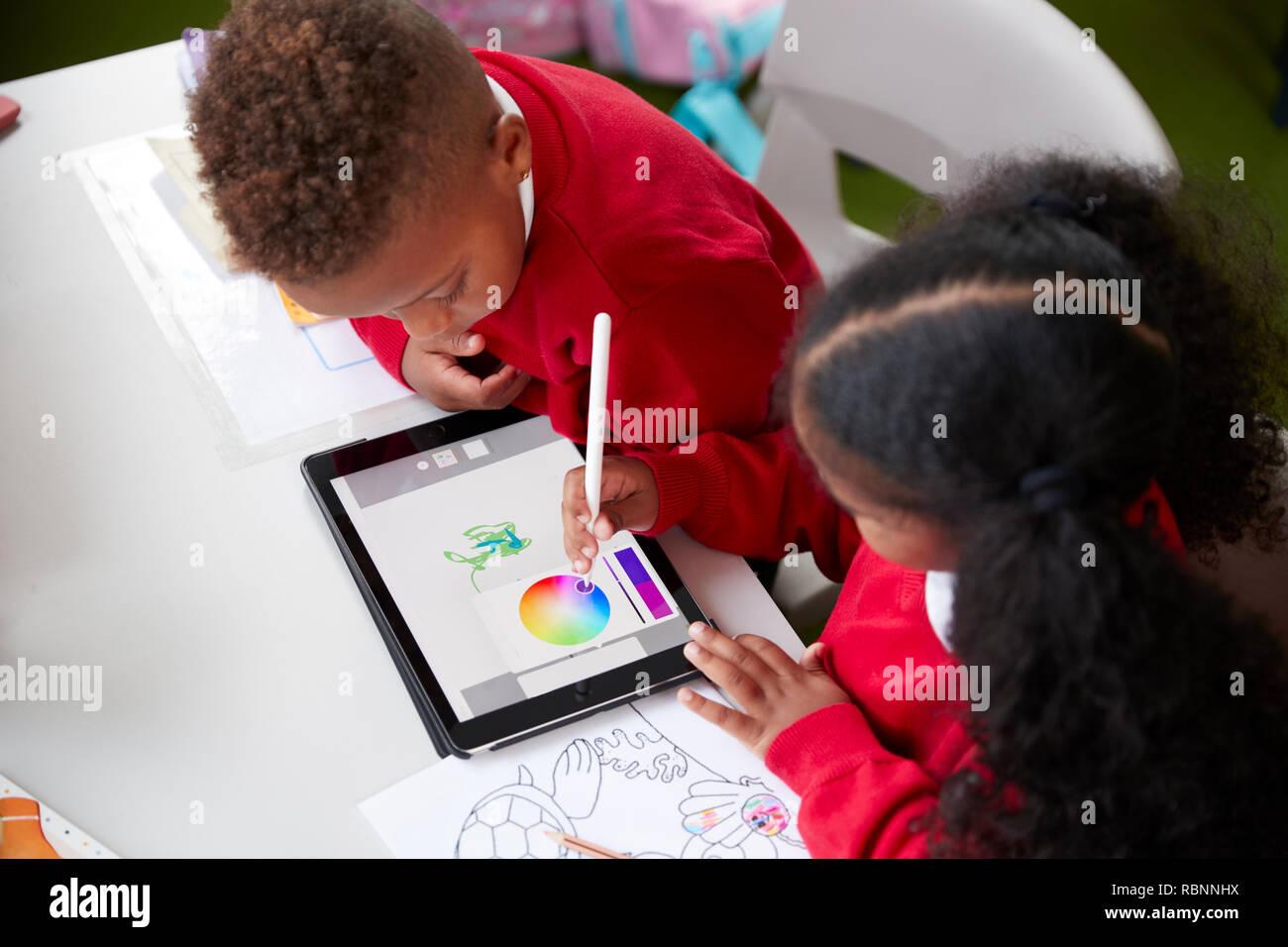 Portrait de l'école maternelle deux enfants assis à un bureau dans un dessin en classe avec un ordinateur tablette et stylet, Close up Banque D'Images