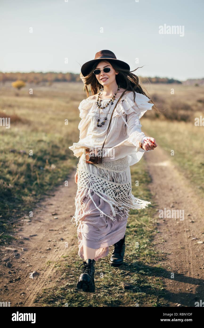 Belle fille hippie dans hat marche sur route dans la nature. Style de la  liberté c2466f01d90