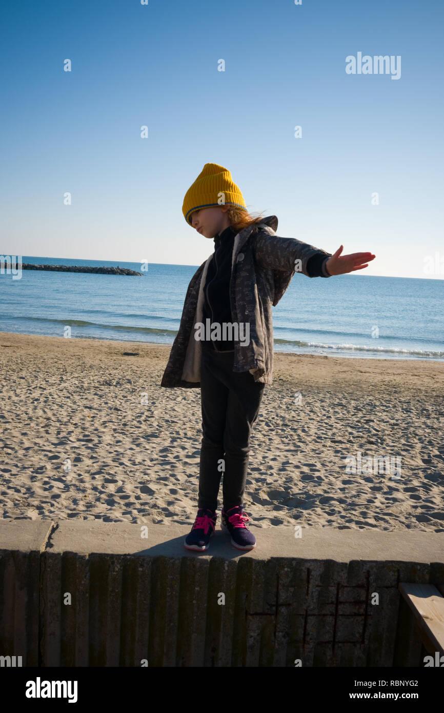 Une fillette de six ans avec yellow hat laineux et anorak se dresse sur une digue tout en faisant semblant de voler. Journée d'automne à Palavas les Flots, France Banque D'Images