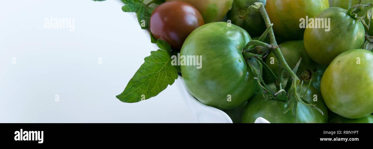 Jardin vert frais mûrs tomates au Bol en céramique blanc, fond blanc et de l'espace pour le texte Photo Stock