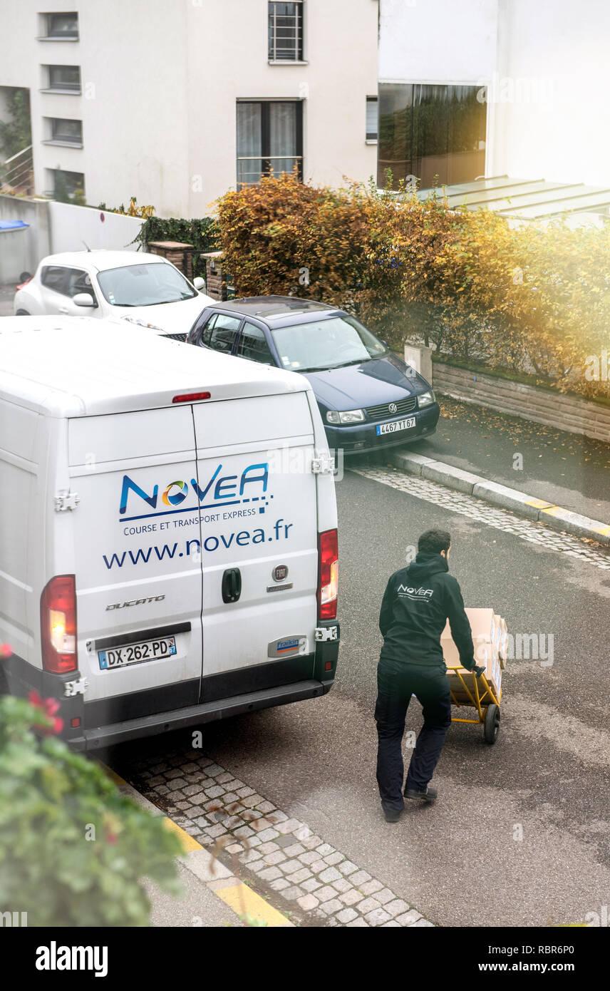 Paris, France - Nov 14, 2018: Man pushing trolley de transport de marchandises de camions de livraison pour une livraison au bureau accueil - view Photo Stock