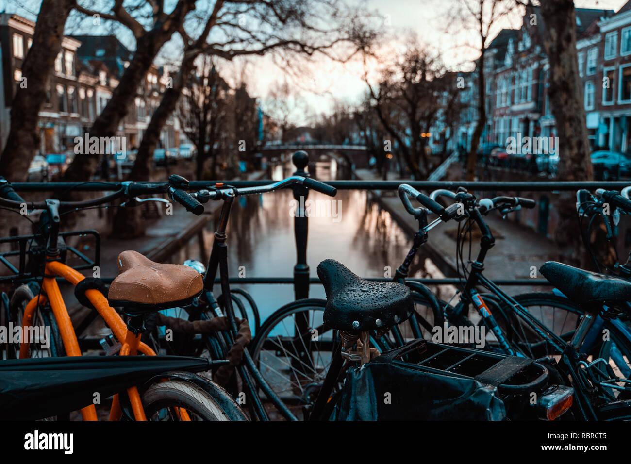 Des vélos sur un pont à Amsterdam, Pays-Bas par temps couvert humide transport destination vacances Banque D'Images