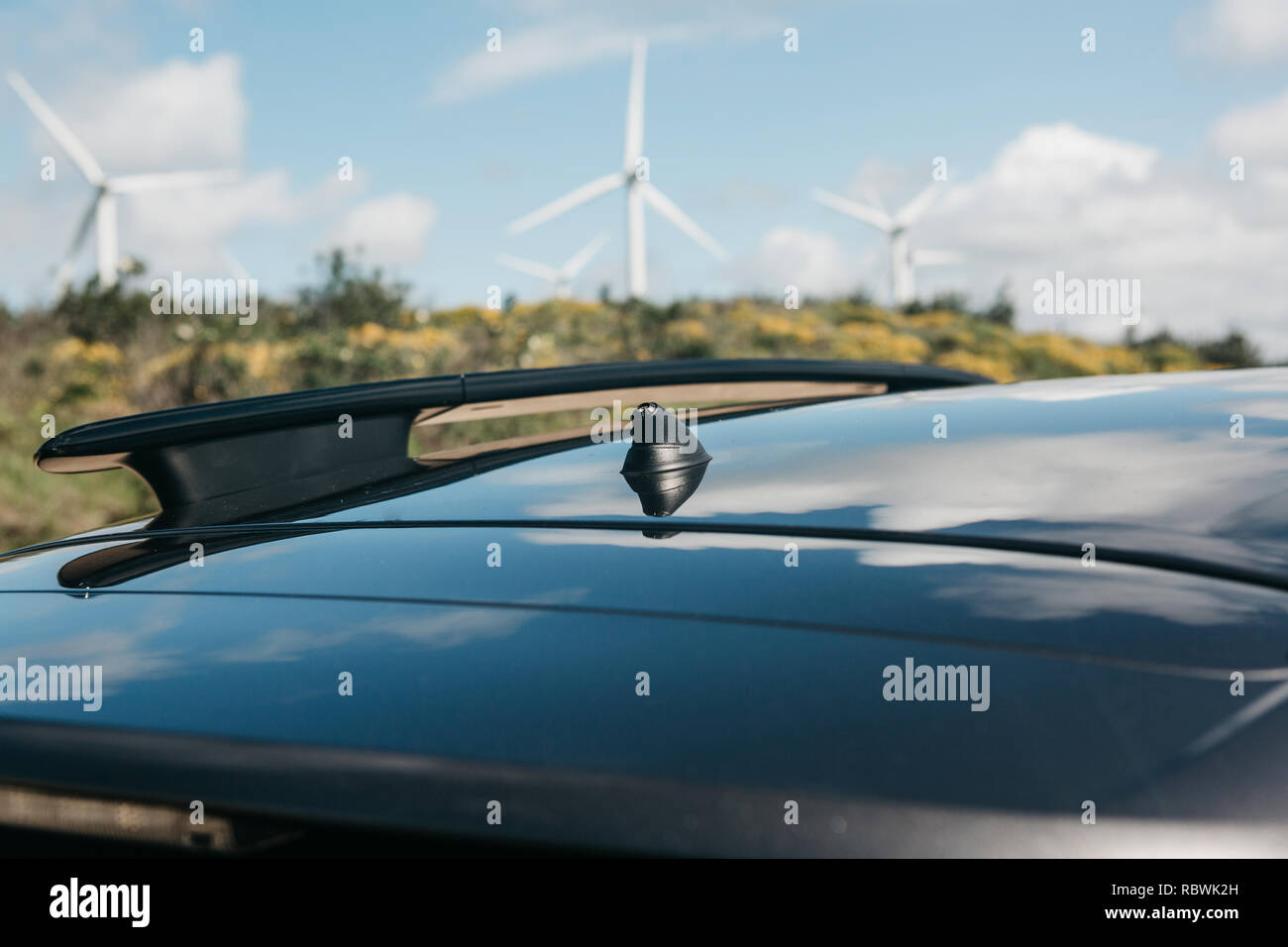 Photo conceptuelle avec une autre perspective avec focus sélectif sur l'antenne sur le toit du véhicule et moulins à vent trouble ou éoliennes dans l'arrière-plan. Photo Stock