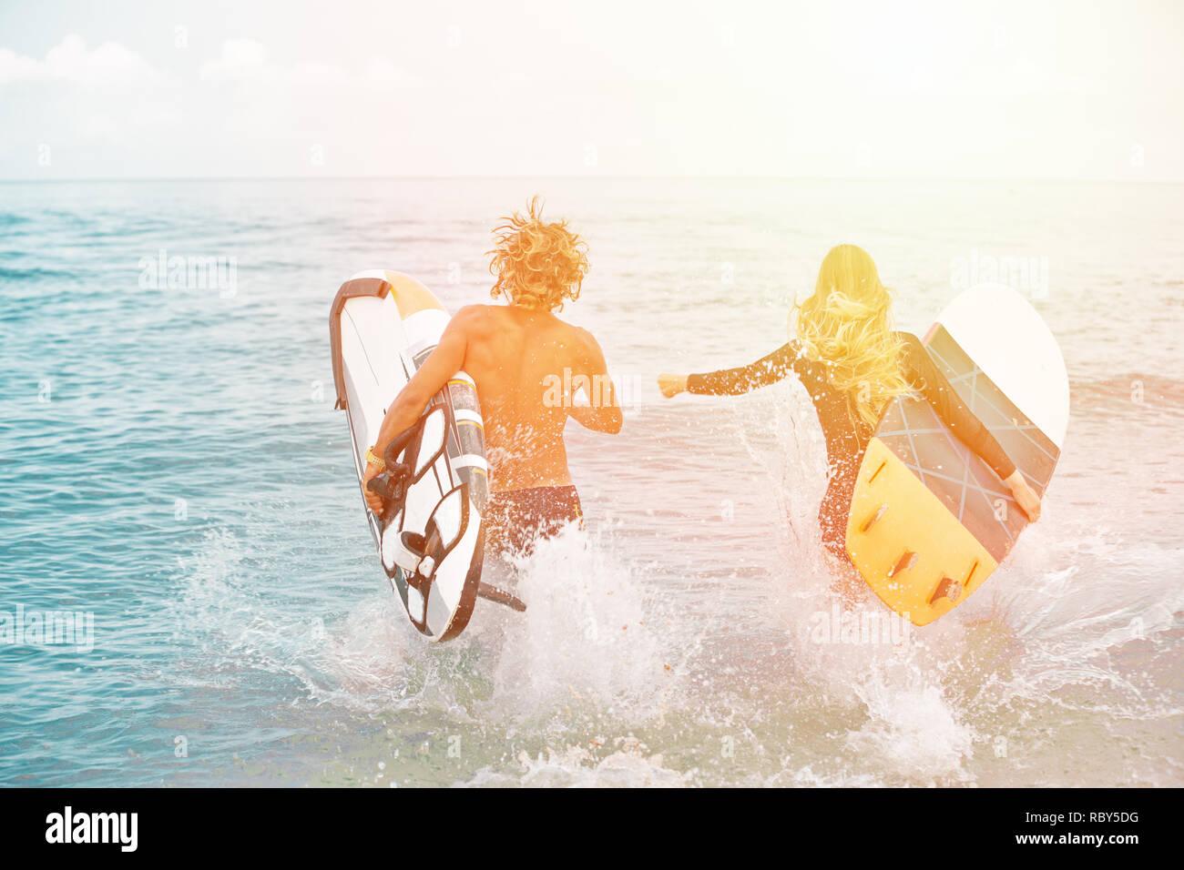Les surfeurs à la plage- Smiling couple de surfers marche sur la plage et s'amuser en été. Sport extrême et vacances Banque D'Images