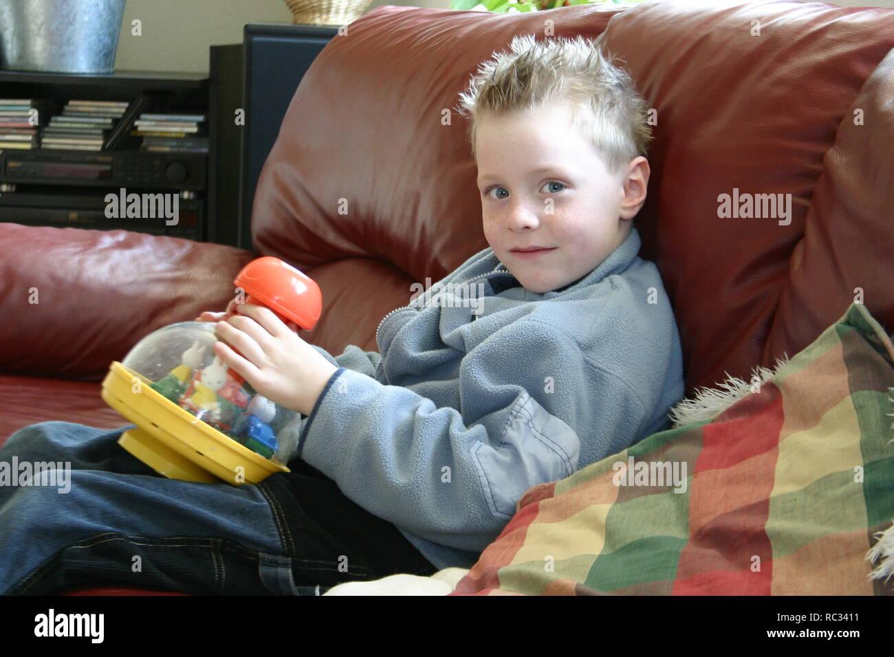 Jeune garçon avec humming top sur canapé à l'intérieur, regardez l'appareil photo Photo Stock