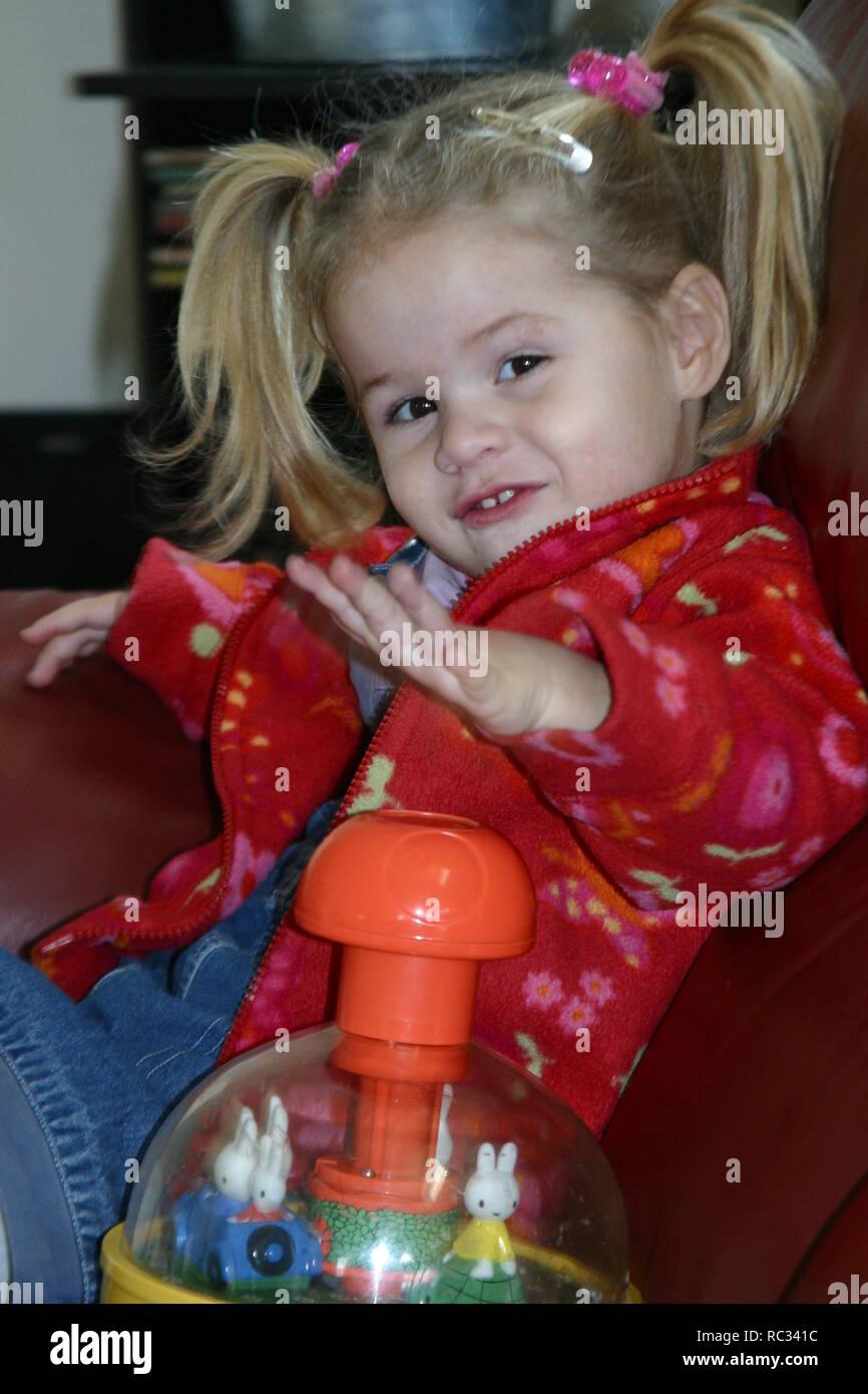 Petite fille jouant avec humming top sur canapé Photo Stock