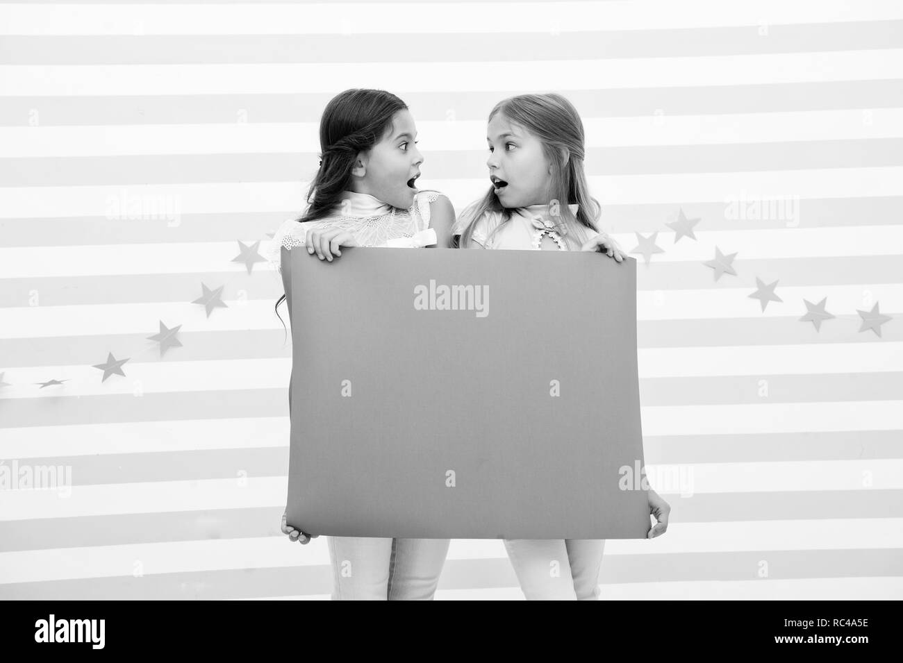 Concept annonce choquante. Surprenant incroyable nouvelle. Tenir fille bandeau publicitaire. Enfants Jeux de filles holding paper banner pour l'annonce. Les enfants surpris choqué avec copie papier de l'espace l'espace. Photo Stock
