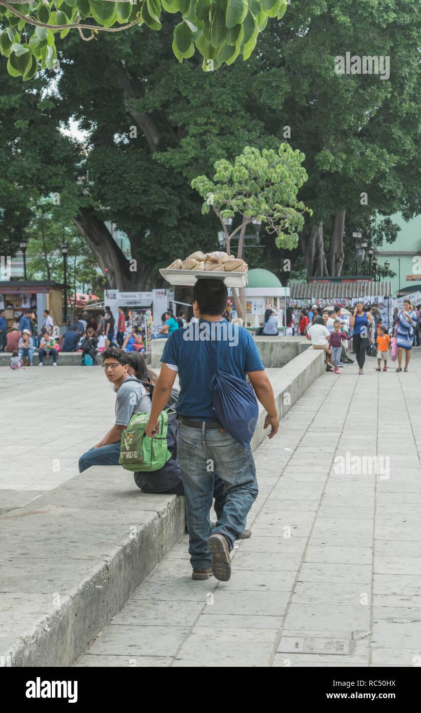 Homme marchant avec un plateau de nourriture sur la tête, près du Zocalo, à Oaxaca, Mexique Photo Stock