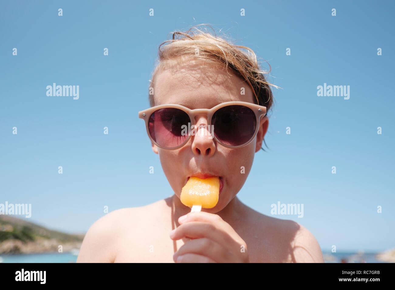 Garçon dans les lunettes de profiter de ice lolly Banque D'Images