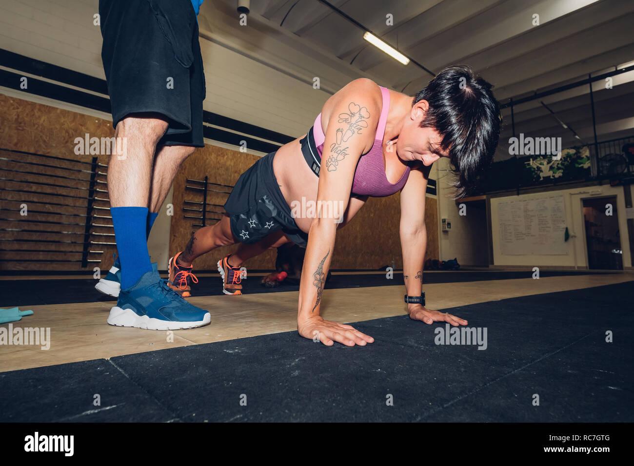Trainer sur femme enceinte faisant pousser ups in gym Banque D'Images