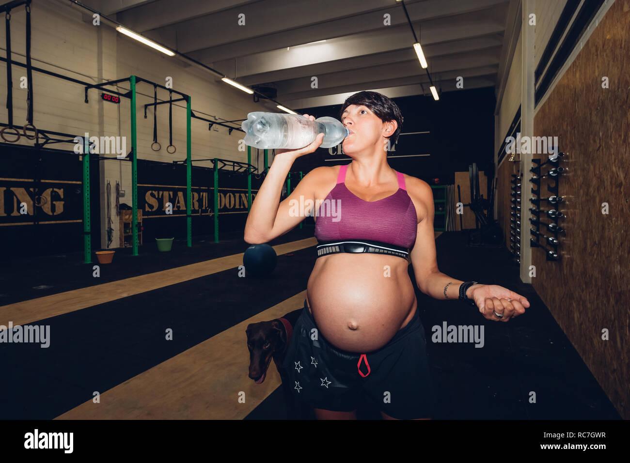 Femme enceinte de boire de l'eau en bouteille de sport Banque D'Images