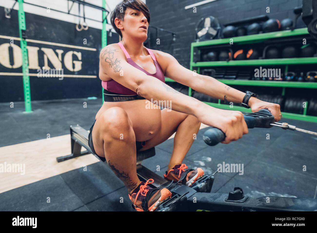 Femme enceinte sur une machine à ramer en salle de sport Banque D'Images