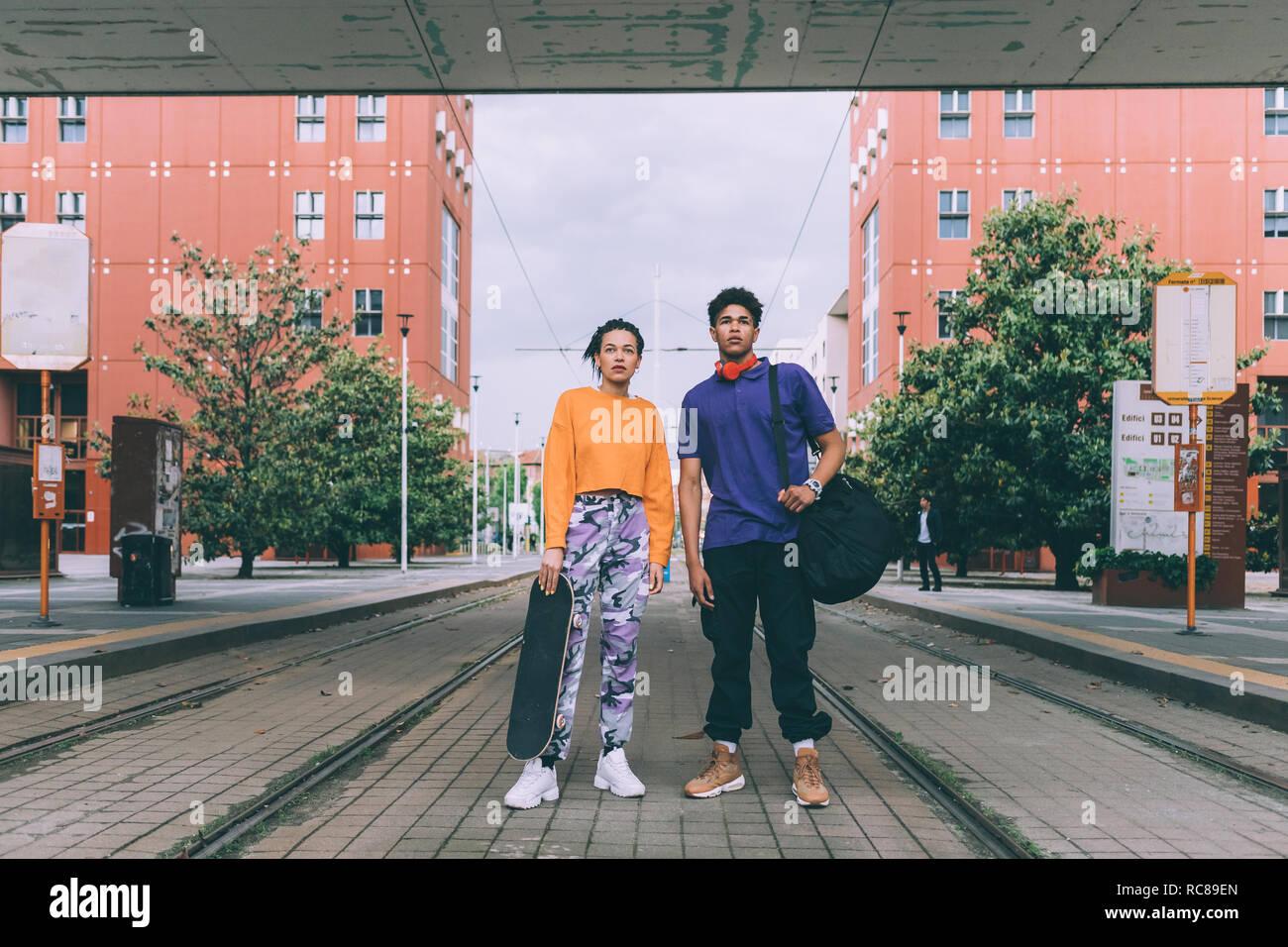 Frère et sœur debout sur voies de tram, Milan, Italie Banque D'Images