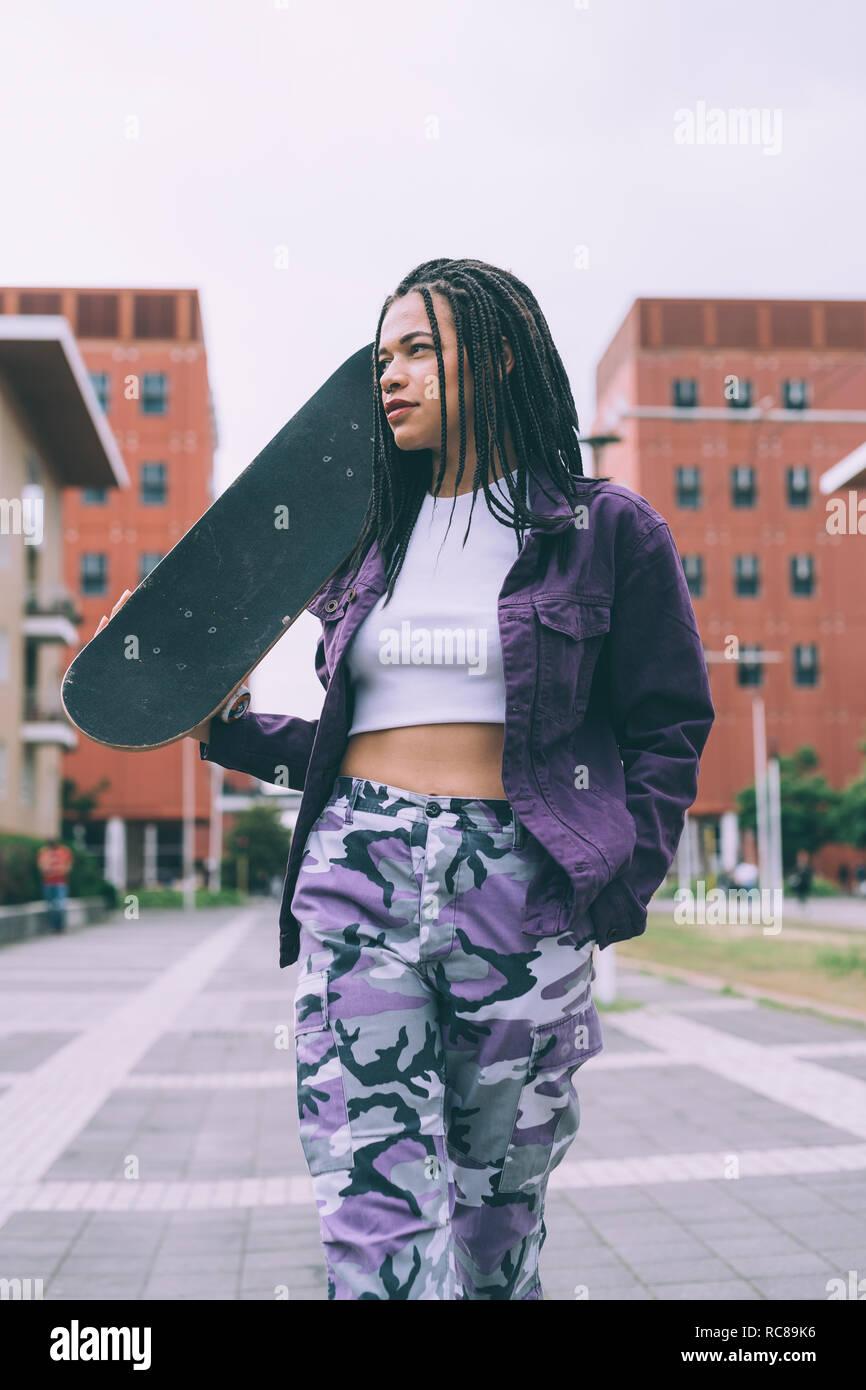 Femme avec skateboard, Milan, Italie Banque D'Images