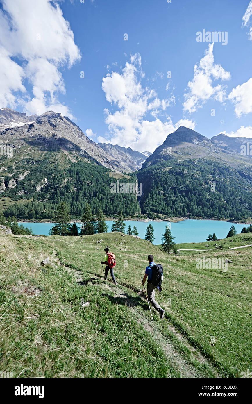 Randonneurs sur champ vert luxuriant, le lac en arrière-plan, le Mont Cervin, Matterhorn, Valais, Suisse Banque D'Images
