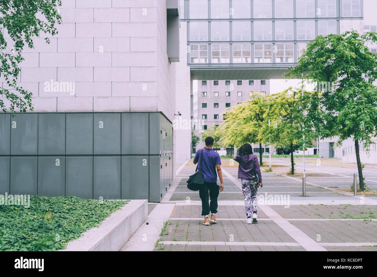 Amis marchant dans la construction complexe, Milan, Italie Banque D'Images