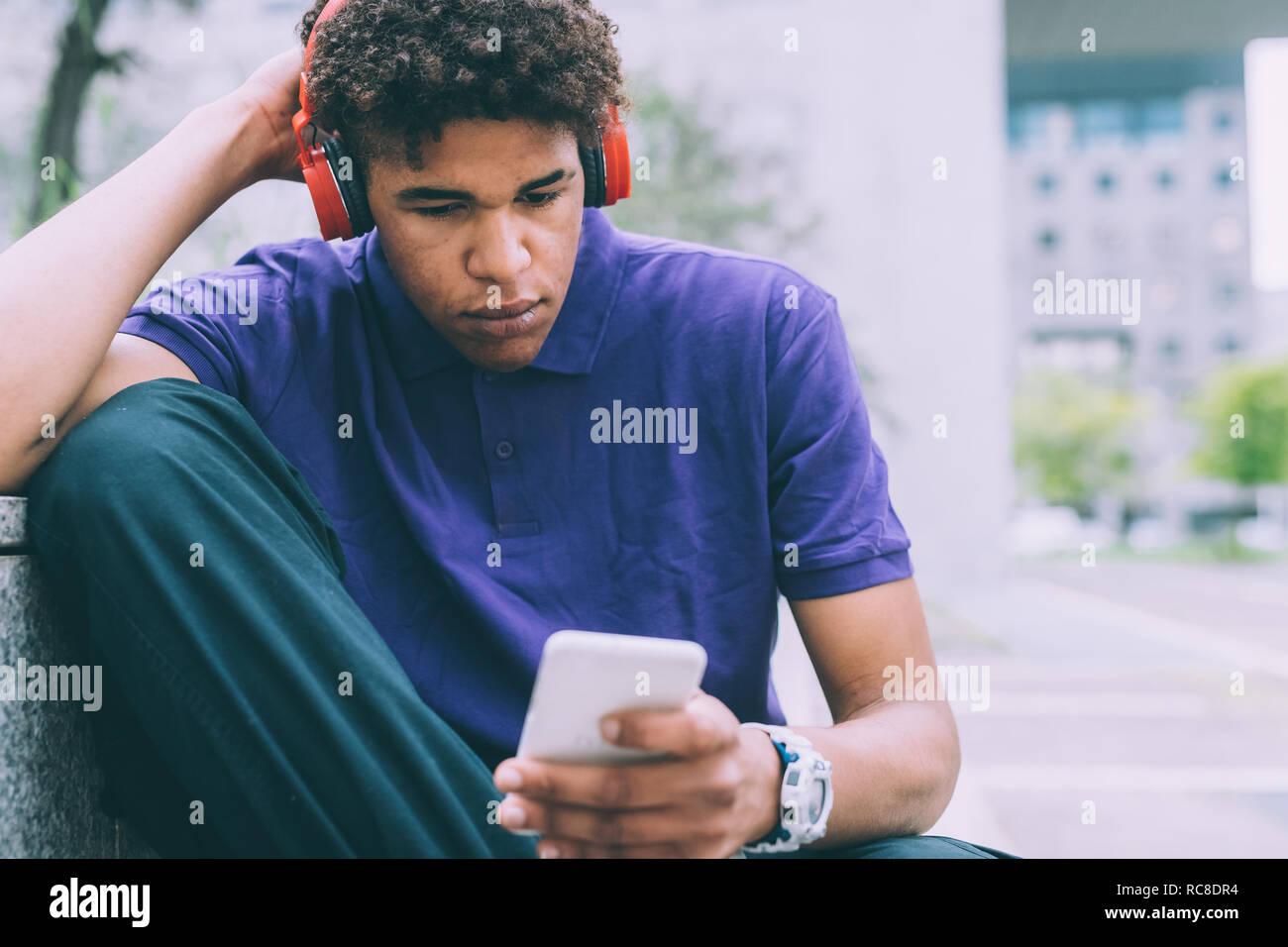 Man texting et de l'utilisation des écouteurs sur banc en béton Banque D'Images